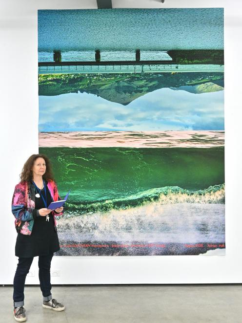 One of the co-ordinators of a Dunedin symposium, Pam McKinlay, stands in front of a photographic...