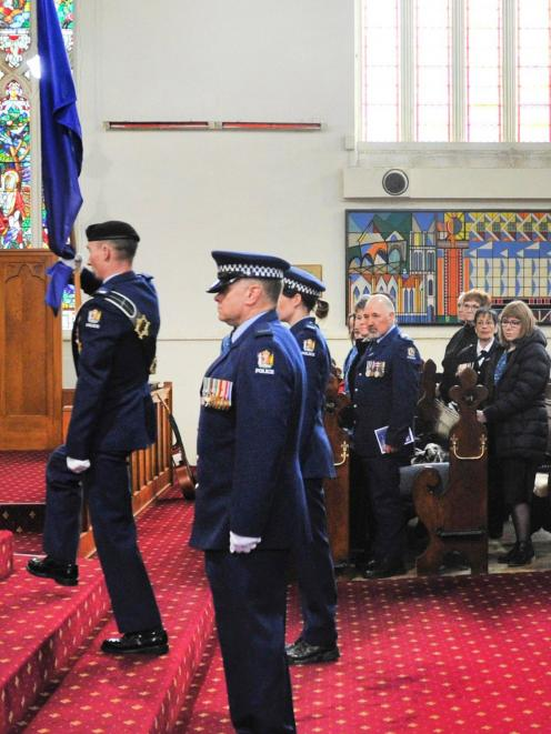 Constable Will Atkinson places the Police Flag at the front of First Church, as Constables Jack...