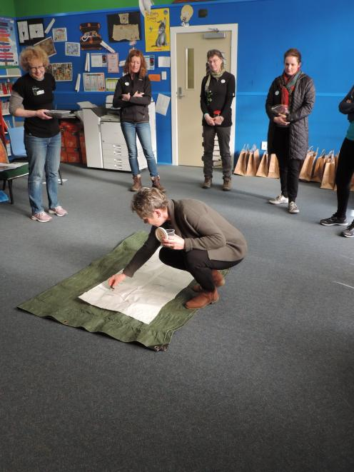 Weston School teacher Jenny Kitchin places soil from her home garden on to a map of Otago during...