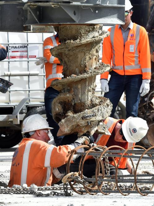 Workers drill the first pile.