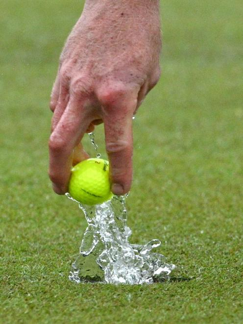 Leith Campion retrieves his ball from the hole during a rain-soaked semifinal of the Otago...