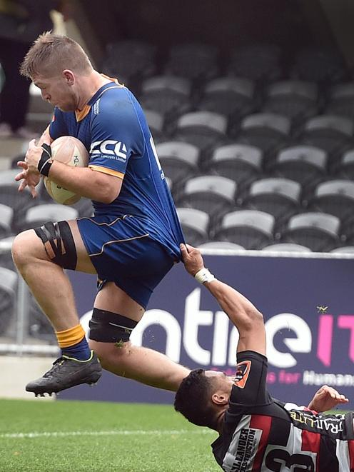 Otago blindside flanker Charles Elton heads towards the tryline as Counties-Manukau centre Sione...