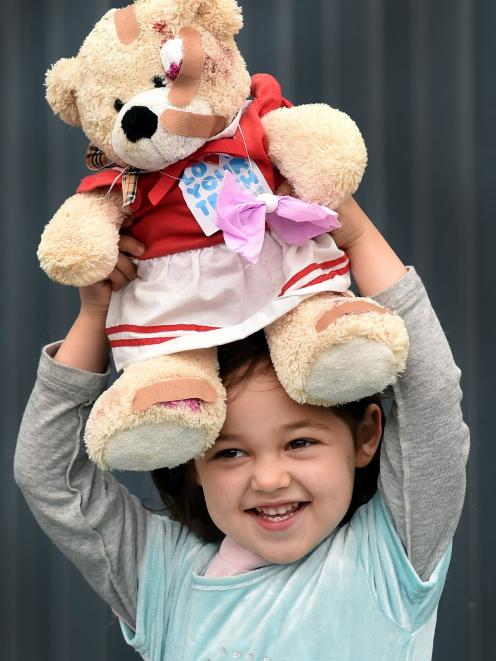 Santia Throp (3) happily holds aloft her bandaged bear after going to the Teddy Bear Hospital in...