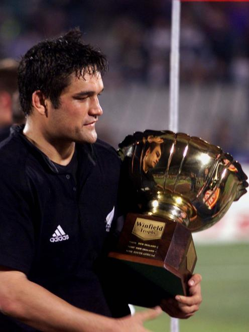 All Blacks captain Taine Randel walks away with a trophy after his team beat South African Springboks during the Tri-Nations Series in 1999. Photo: Reuters