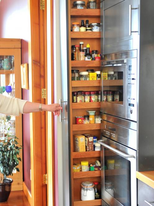 The spice rack built by Michael Landmann vanishes back into the kitchen cabinetry.