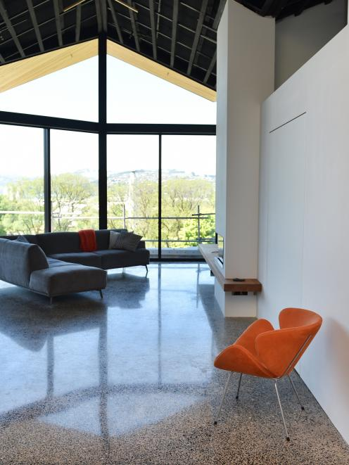 The polished concrete floor has stones gathered from local beaches. A space-saving swivel door is...