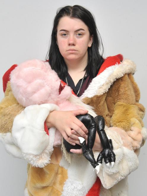 Tess Wing tries on the heavy coat made of stuffed animals while 