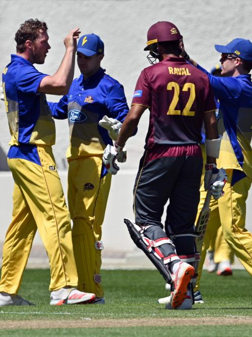 Raval is bowled by Otago paceman Matt Bacon who then (left) celebrates with team-mates Mitch...