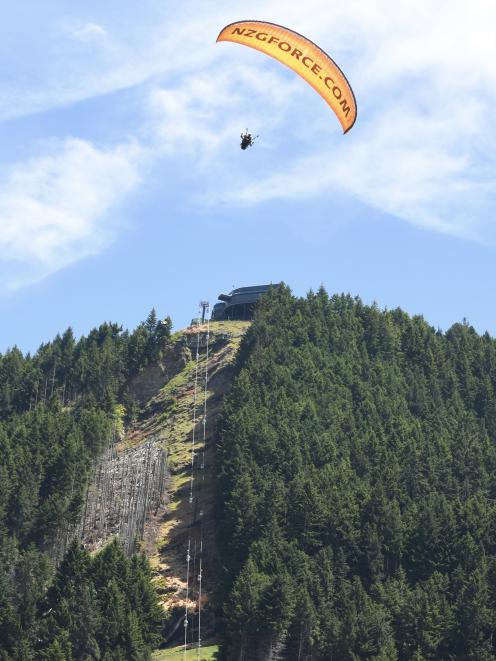 A paraglider flies above Ben Lomond, where Skyline Enterprises is doing preparatory work for its...