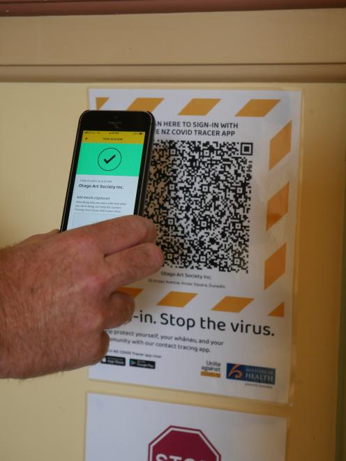 A member of the public scans a QR code using the NZ Covid Tracer app.PHOTO: JESSICA WILSON