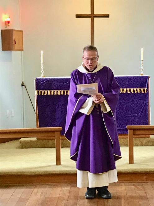Anglican Bishop of Dunedin Steven Benford reads the formal document of deconsecration.