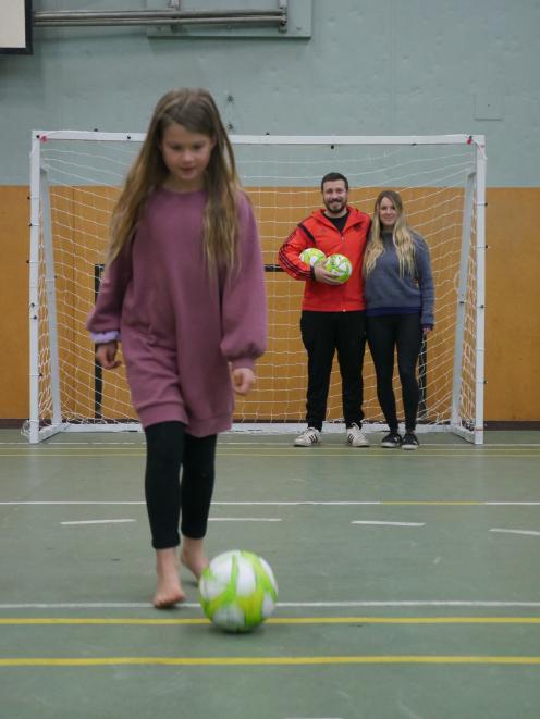 Sienna Sainsbury (8) kicks a ball while her parents and Dunedin Futsal Academy founders Maxi...