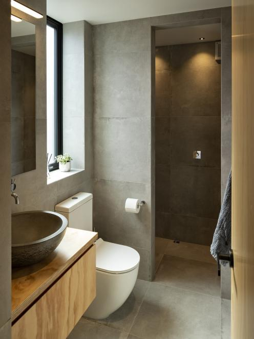 The wet-room style of the compact bathroom is reminiscent of a Japanese spa, with floor-to...