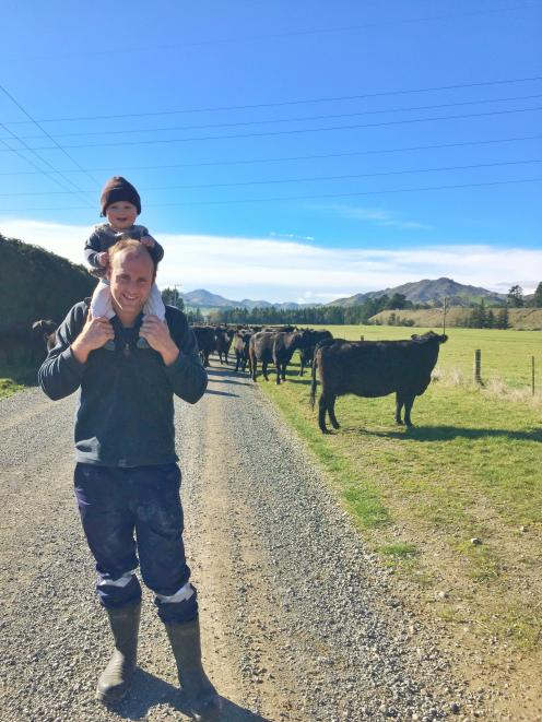 Hurunui farmer Stu Fraser, with his son Jock (2), was pleased to finally get a decent downpour...