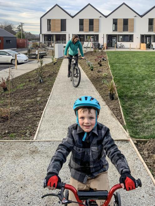Arlo Ross (5) and his mother, Philippa, head out on a bike ride. Shutters on the exterior of the...