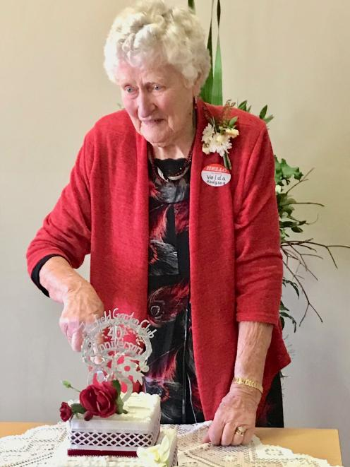 Velda Hodgson (88), a member of the Fairfield Garden Club for 38 years, cuts the cake at the club...