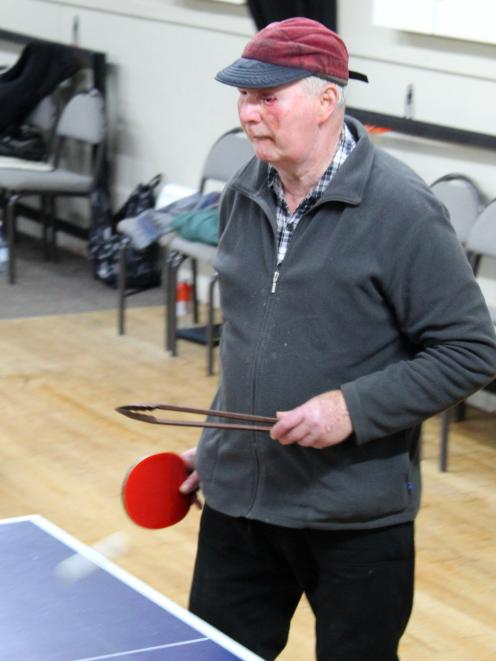 Bill Thomson, of Mosgiel, goes to pick up the ball using a set of kitchen tongs at Mosgiel Table...