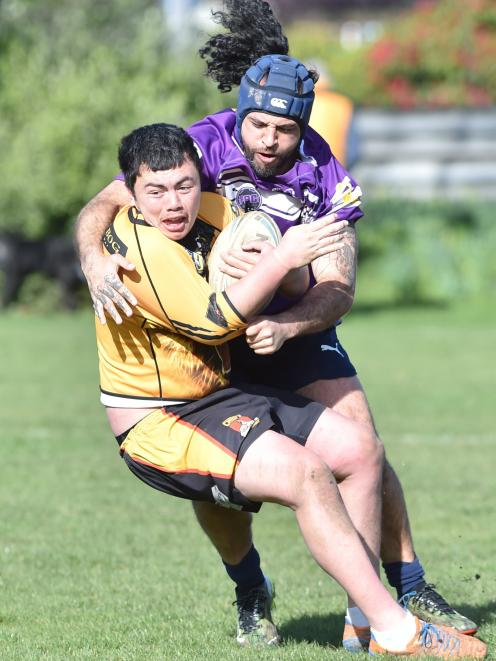 Kia Toa Tigers player Aiden Muraahi tries to escape the clutches of South Pacific Raiders...