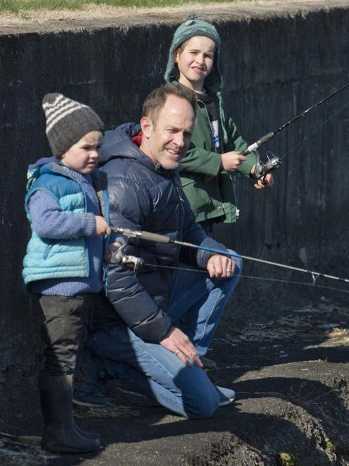 The Dukes family (from left) Claude (4), Breton and Hector (6) wait patiently to reel in a fish....