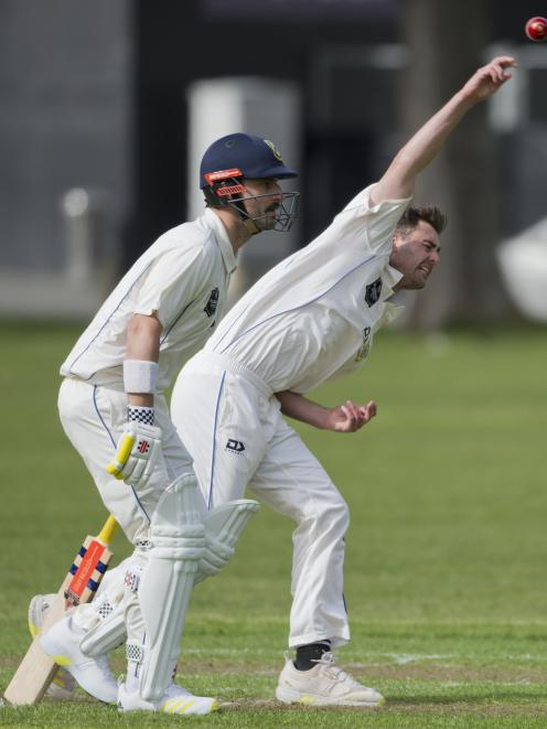 Otago seamer Travis Muller sends down a delivery while senior batsman Hamish Rutherford waits at...