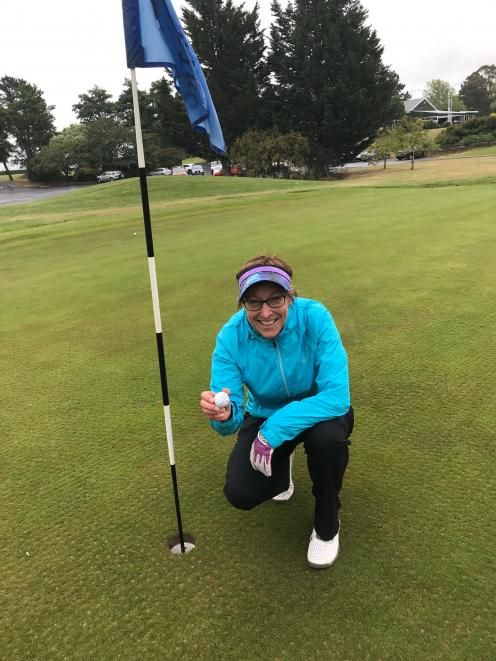 Mosgiel woman Tania Stevens, of Taieri Lakes Golf Club, removes the ball from No 7 hole after her second hole in one on the front nine. Photo: Supplied
