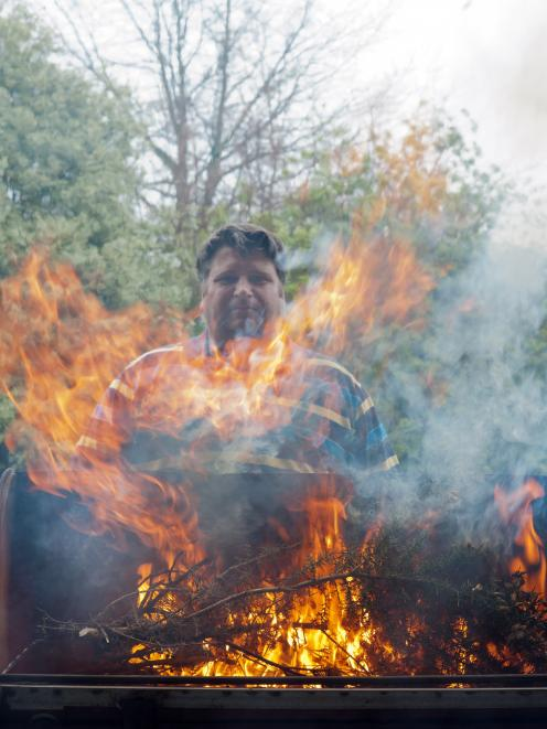 Dr Tim Curran assess the flammability of gorse on his barbecue. Photo: David Hollander