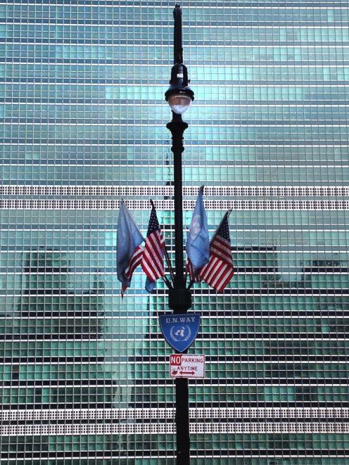 UN flags on a street lamp in front of the Secretariat Building at the United Nations in New York....