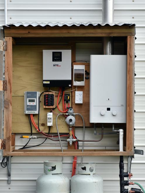 The power hub for the home is mounted on one end of the house.