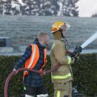 Queenstown man Jonathan Dunoyer assists a firefighter at Jacks Point yesterday. Photos by Blair Pattinson.