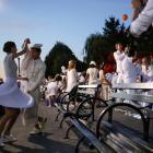 People attend Diner En Blanc, the French-inspired secret pop-up dinner, in Robert F. Wagner Jr....