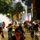 People run from flash-bang grenades in uptown Charlotte, North Carolina, during a protest of the...