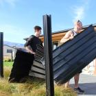Cromwell residents Ben Cormack (left) and Nathan Manning clear up the remains of a neighbour's fence which was almost completely destroyed by a series of tornadoes in the town. Photos by Jono Edwards.