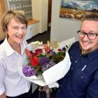 Mike's Couriers owner Mike Williamson delivers a bouquet of flowers to Margaret Mulholland in the...