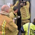 Firefighters jemmy a lift door to provide fresh air to nine people trapped in an elevator between the 5th and 6th floors of the Burns Building in the Octagon. Photo: Gerard O'Brien