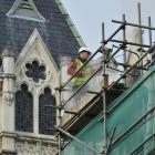 A worker steam-cleans the Oamaru stone beside the tower. Photos: Gerard O'Brien.