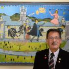 Prof John Broughton, CNZM, stands in front of a painting by Ivan Hill depicting the professor and...