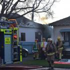 Crews attend a house fire in South Dunedin yesterday. Photos: Peter McIntosh