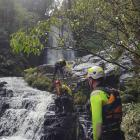 Members of a water rescue team abseil and search for Stephen Lowe at the McLean Falls in the...