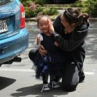 Ashley Papara embraces her daughter Tilly after she was rescued by firefighters from a car parked...