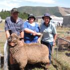 David Howden, of Gore, holds the two-tooth Romney ram sold by his daughter, Julie Howden (centre), as she and Christchurch buyer Janice Winter seal the $375 deal with a handshake. Photos: Sally Brooker