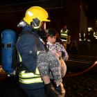 An Airport Emergency Service officer carries Teane Ellison (9) from the wreckage of a plane...