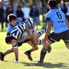 Otago Boys' High School First XV hooker Harry Hansen gets tackled by King's High School First XV lock Sam Stewart with flanker Sabin Reynolds in support during the traditional interschool fixture yesterday. Photos: Peter McIntosh