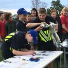 AgriKids NZ grand final winners Henry Gray (writing), Austin Watson and Tim Connelly-Whyte (feeding the lamb), of Ashburton Intermediate School,  multi-task during an agri-challenge competition against three school staff. The boys won the challenge. Photo
