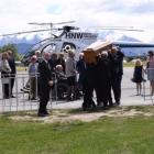The family of Nick Wallis arrive at the funeral while his coffin is carried into the venue. Photo...
