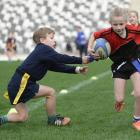 Sylvie Haig (8), of Fairfield School, tries to avoid the lunge by William Henderson (7), from the Columba College-John McGlashan College combined team. Photos: Gerard O'Brien