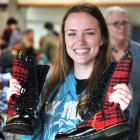 Holding a pair of near-new Doc Marten shoes bought for less than 50c is University of Otago...