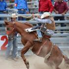 Sam Leslie, of Lawrence, concentrates on staying on in the second division saddle bronc event at...