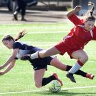 Poppy Bell (15, left), of Otago Girls' High School, goes for the ball along with Maddy Neal (17),...