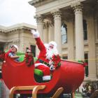 Santa Claus and his helpers make their way past the crowds at the Oamaru Christmas parade...