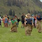 Kiwa Tuhoro (left) bounces past his competition in the sack race at the Kurow Races yesterday....